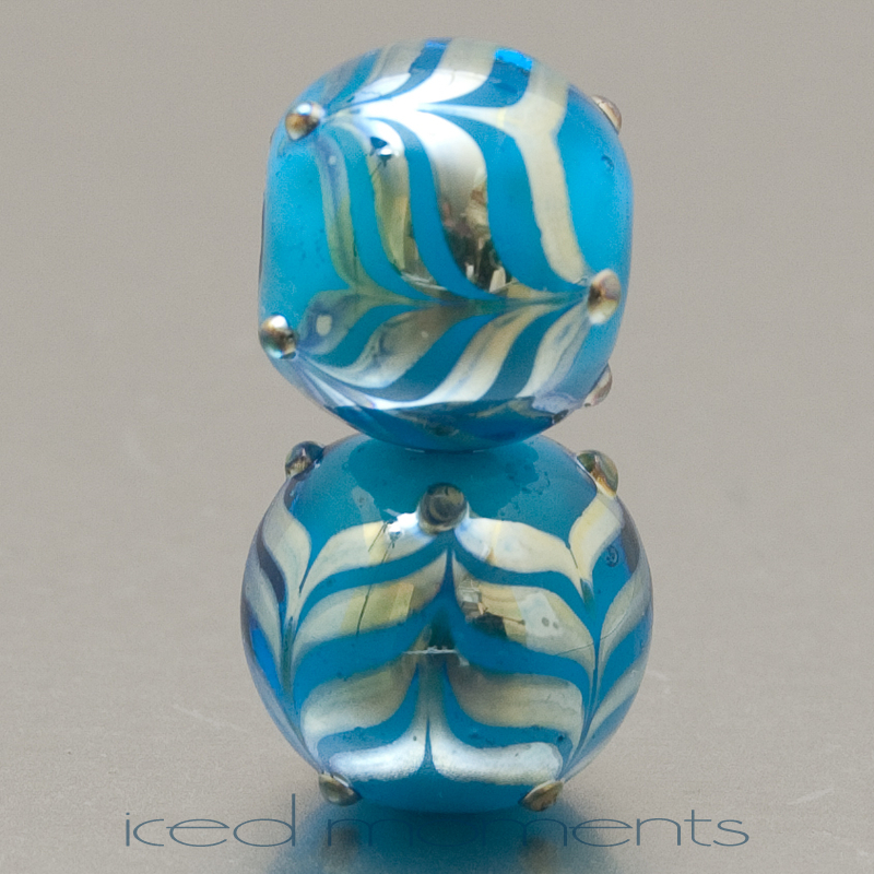 Bead pair: aqua encased, with silver glass feathers